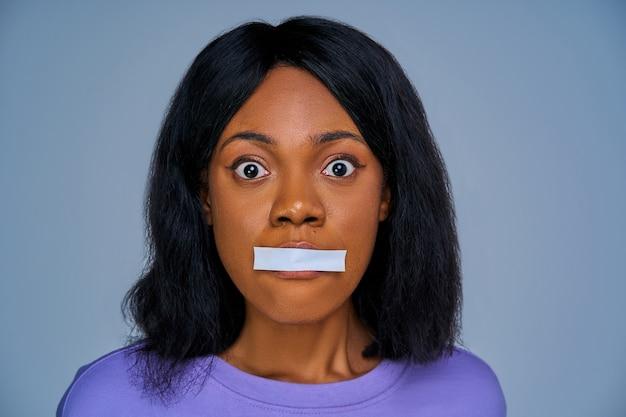 Nahaufnahme erschrockenes weibliches gesicht mit versiegeltem mund durch weißen streifen. emotionskonzept