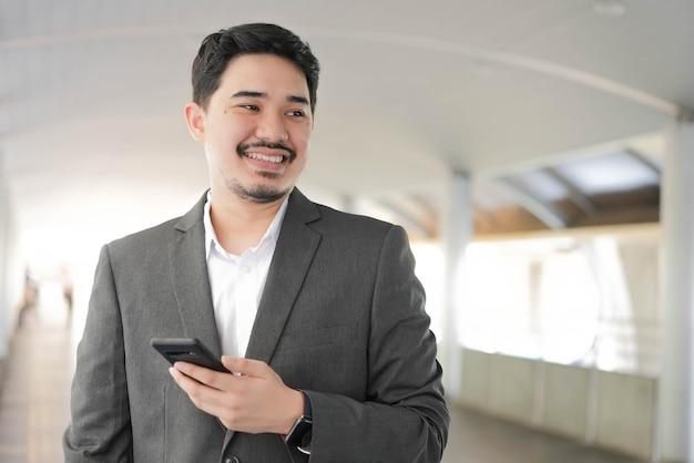 Nahaufnahme erwachsener geschäftsmann aus dem nahen osten hält smartphone und steht außerhalb des büros in entspannungszeit für lifestyle-geschäftskonzept