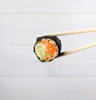 Nahaufnahme essstäbchen und sushi-rolle mit unscharfem hintergrund