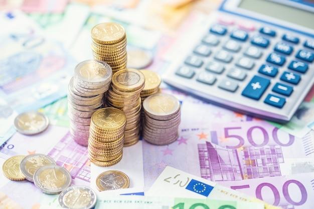 Nahaufnahme-euro-münzen und -banknoten mit taschenrechner.
