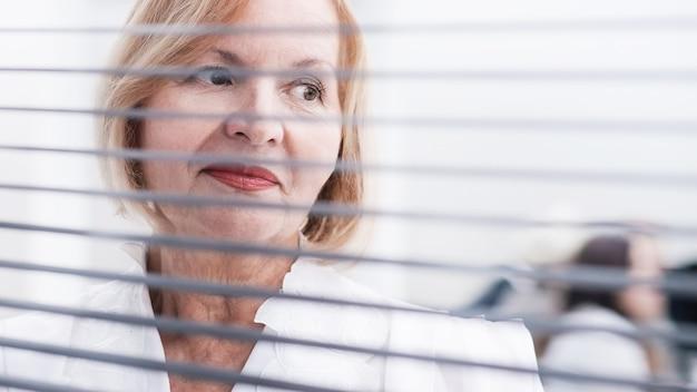 Nahaufnahme. exekutive geschäftsfrau, die nahe bürofenster steht. geschäftsleute