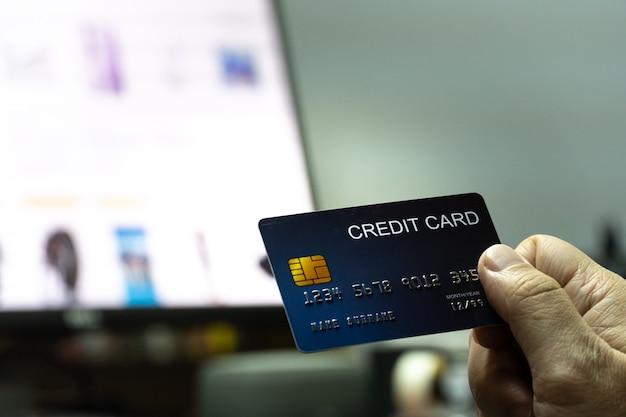 Nahaufnahme flach fokussierte hand halten kreditkarte mit computertastatur