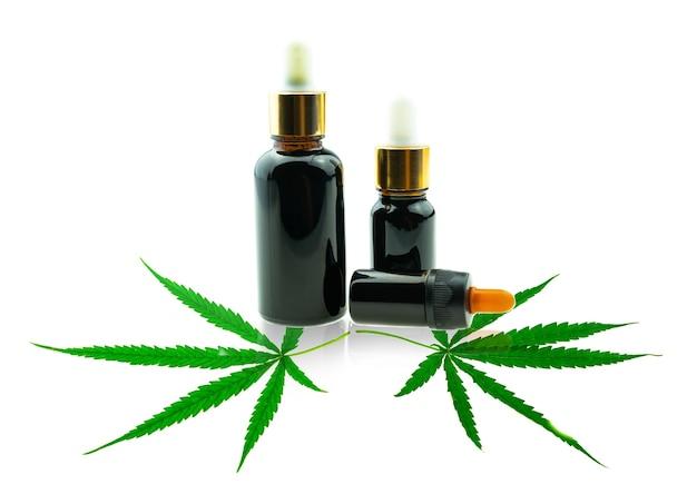 Nahaufnahme flasche mit cbd-öl und cannabisblatt auf weißem hintergrund, medizinisches marihuana-konzept