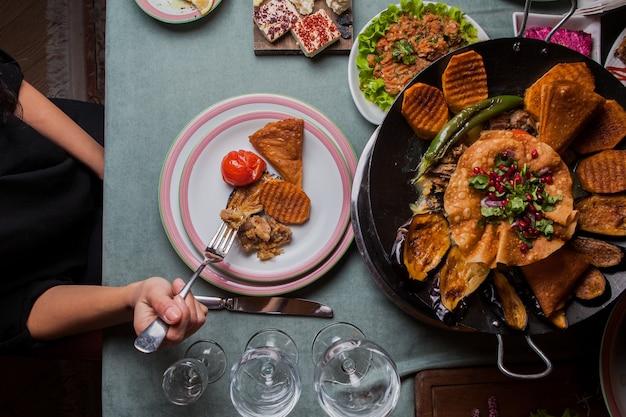 Nahaufnahme fleisch mit ofenkartoffeln, auberginen, tomaten, pfeffer und mit granatapfel in einem teller auf serviertisch dekoriert