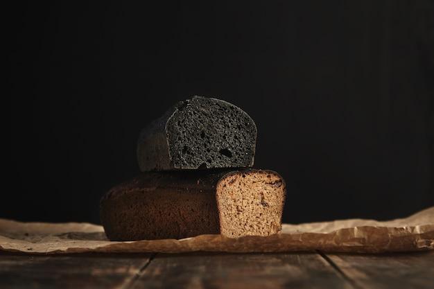 Nahaufnahme fokus auf zwei frisch gebackene diät gesunde brote. holzkohle und roggen mit feigen, isoliert auf schwarz, präsentiert auf rustikalem holztisch