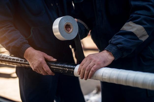 Nahaufnahme fokussieren handansicht von professionellen industriearbeitern, die meta-rohr mit klebeband verbinden.