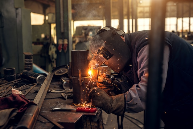 Nahaufnahme fokussierte seitenansicht des professionellen maskengeschützten schweißers, der in der werkstatt arbeitet.