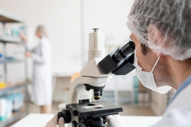 Nahaufnahme forscher, der mit mikroskop arbeitet