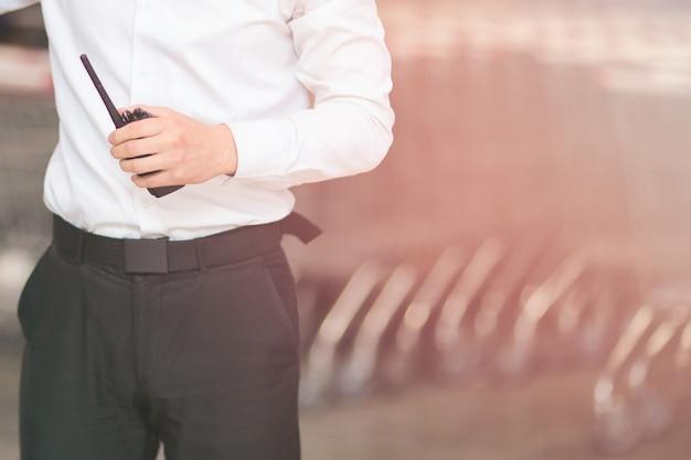 Nahaufnahme foto des mannes in einem weißen hemd und einer schwarzen hose wachmann mit walkie-talkie.