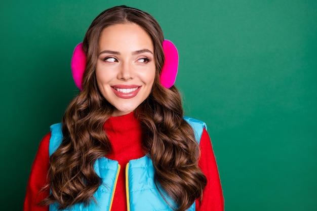 Nahaufnahme foto einer charmanten hübschen jungen dame, die lächelnd interessierte blicke seitlich leerer raum beobachtet, schneefall trägt rosa ohrwärmer blaue weste roter pullover isoliert grüner farbhintergrund