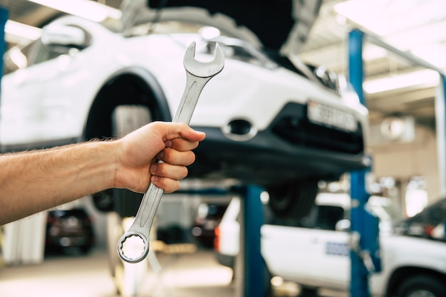 Nahaufnahme foto einer männlichen automechaniker hand mit einem gabelschlüssel auf dem hintergrund der reparatur eines autos