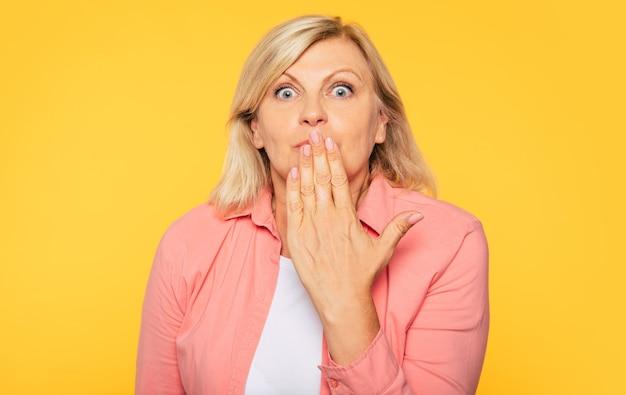 Nahaufnahme foto einer schönen blonden seniorin, während sie den finger auf ihre lippen hält und stille geste auf gelber wand zeigt