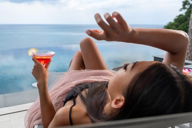 Nahaufnahme: foto eines entspannten mädchens, das mit einem glas des kosmopolitischen cocktails auf einem hintergrund des verschwommenen meeres liegt. tropischer urlaub