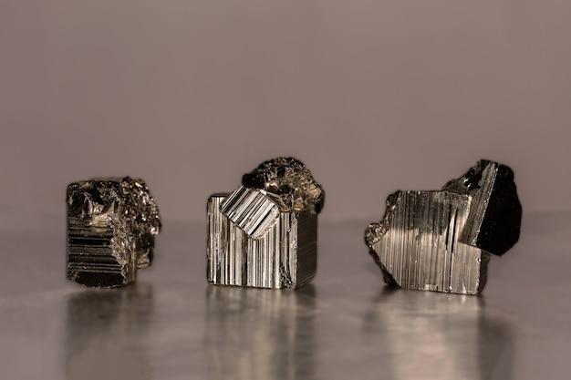 Nahaufnahme foto eines pyritminerals auf reflektierender oberfläche. es kommt in kubischen, pentagonododekaedrischen oder oktaedrischen kristallen vor, manchmal mit abwechselnd längsgestreiften seiten