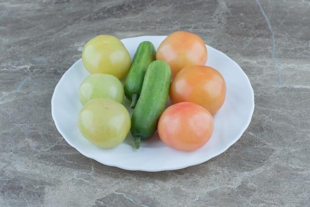 Nahaufnahme foto frische gurken und unreife tomaten.