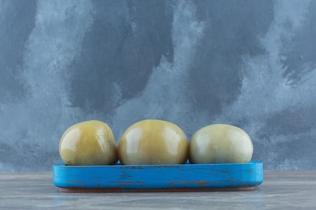 Nahaufnahme foto grüne tomate auf blauem holzbrett.