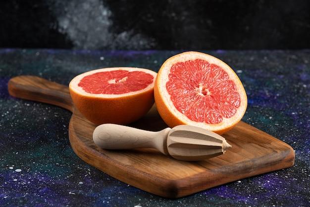 Nahaufnahme foto halb geschnittene grapefruit auf holzbrett.