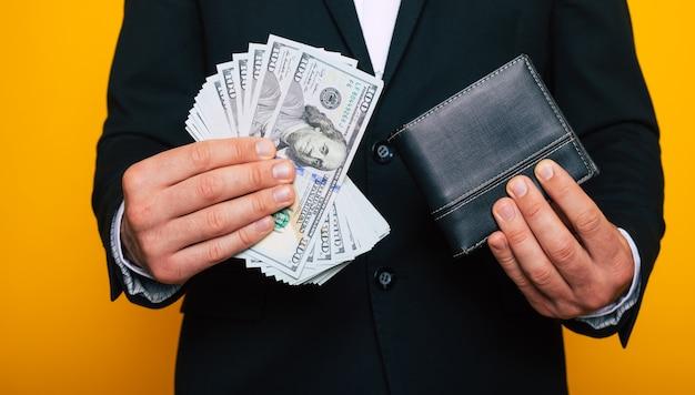 Nahaufnahme foto junger erfolgreicher geschäftsmann hände mit brieftasche und bündel von us-dollar