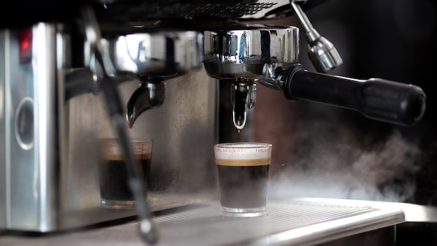 Nahaufnahme foto kaffee zubereiten mit maschine im café. professionelle moderne espresso-kaffeemaschine gießt heißes getränk in die tasse. konzeptkaffee im café.