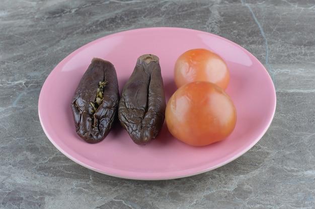 Nahaufnahme foto von auberginen und tomaten in dosen auf rosa teller.
