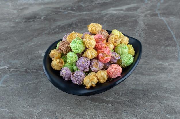 Nahaufnahme foto von bunten hausgemachten bonbons in schwarzer schüssel.