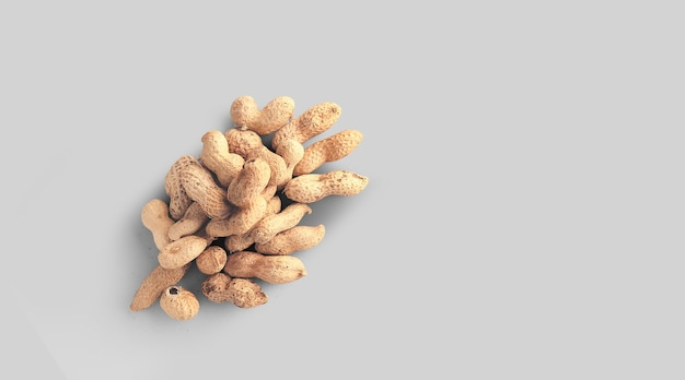 Nahaufnahme foto von draufsicht erdnüsse, rohe erdnüsse in den nussschalen auf grauem hintergrund isoliert.