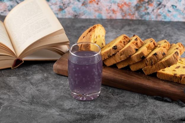 Nahaufnahme foto von frischem traubencocktail mit geschnittenem kuchen und buch über grauem tisch.