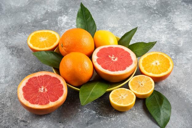 Nahaufnahme foto von frischen zitrusfrüchten in schüssel. ganz oder halb geschnitten.