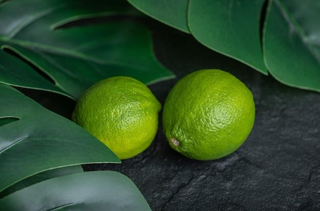 Nahaufnahme foto von frischer limette mit grünen blättern auf schwarzem hintergrund