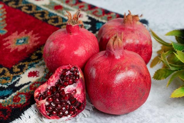 Nahaufnahme foto von geschnittenen oder ganzen granatäpfel über alten teppich.