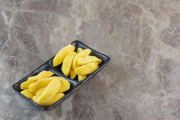 Nahaufnahme foto von haufen von gelben süßen geleebonbons auf schwarzem teller.