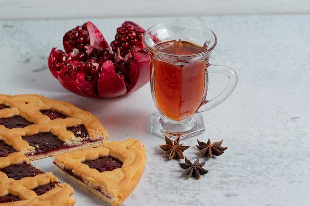 Nahaufnahme foto von hausgemachtem obstkuchen mit tee und geschnittenem granatapfel.