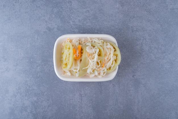 Nahaufnahme foto von hausgemachtem sauerkraut in weißer schüssel über grau.