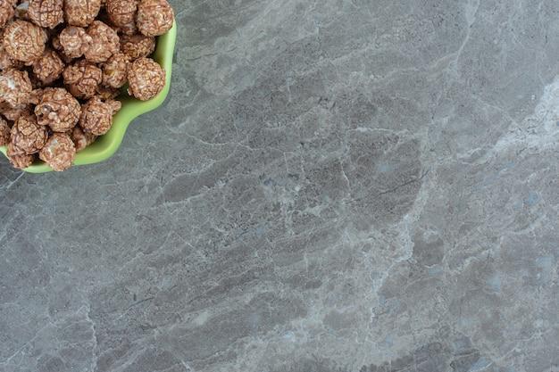 Nahaufnahme foto von hausgemachten frischen bonbons in schüssel über grauem tisch.