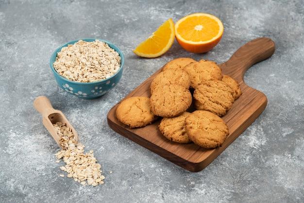 Nahaufnahme foto von hausgemachten keksen auf holzbrett und haferflocken mit orangen über grauem tisch.