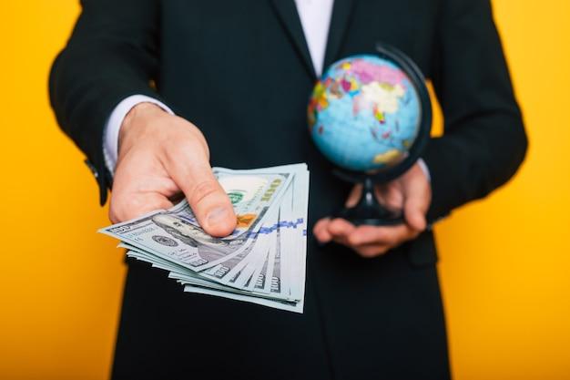 Nahaufnahme foto von jungen männlichen händen halten die vielen dollar der usa isoliert auf gelbem hintergrund