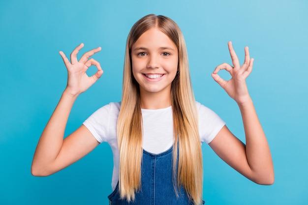 Nahaufnahme foto von niedlichen optimistischen teenager blonden langen haaren mädchen zeigen okey zeichen tragen weißes t-shirt isoliert über pastellblauem hintergrund