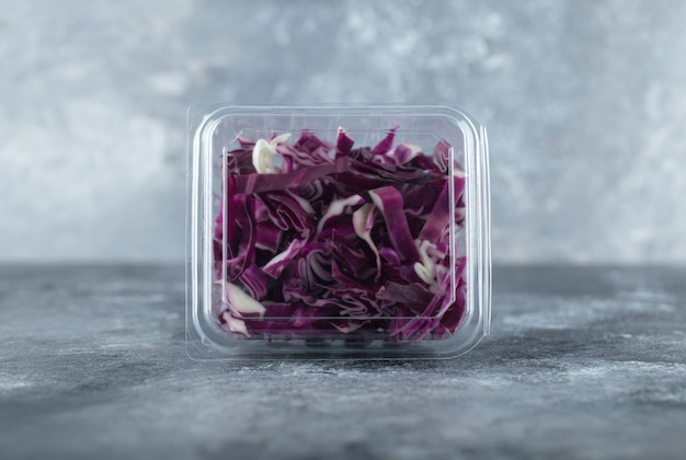 Nahaufnahme foto von plastikbehälter voll mit gehacktem purpurkohl o grauem hintergrund.