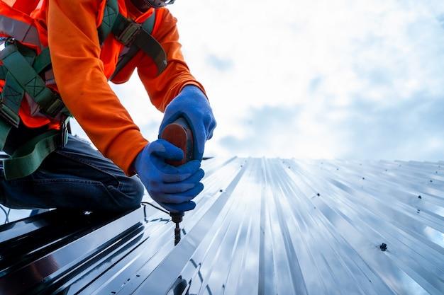Nahaufnahme foto von professionellen und qualifizierten dachdecker in schutzkleidung tragen elektrische bohrmaschine, um das blech auf dem neuen dach des neuen modernen hochbaus zu installieren.