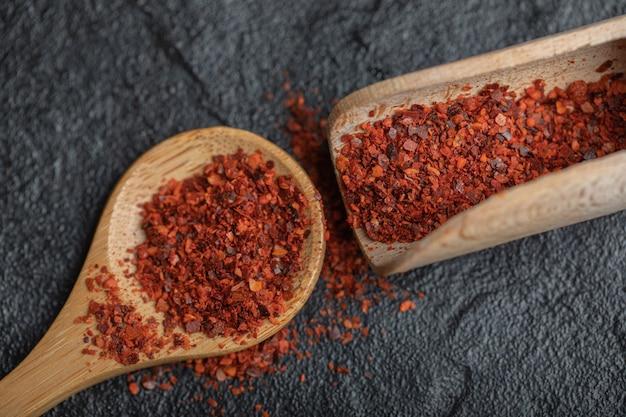 Nahaufnahme foto von red hot chili pepper mit holzlöffel auf schwarzem hintergrund.