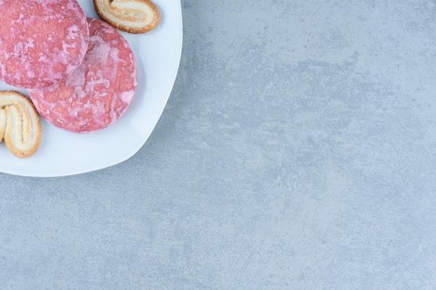 Nahaufnahme foto von rosa keksen auf weißem teller