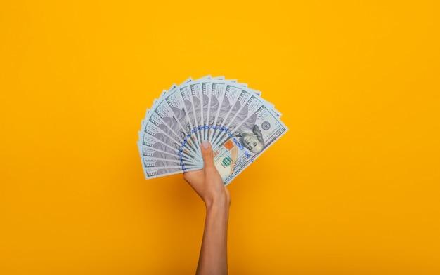 Nahaufnahme foto von schönen weiblichen händen halten den haufen us-dollar isoliert auf gelbem hintergrund. wirtschafts-, geschäfts- und finanzkonzept