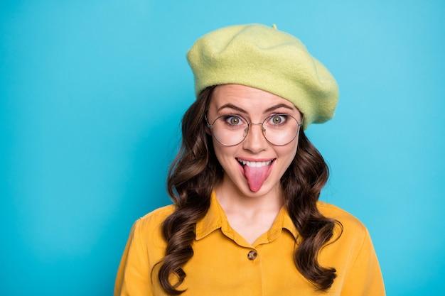 Nahaufnahme foto von sorglosen teenager-mädchen täuschen show zunge heraus tragen gut aussehende kleidung isoliert über blauem hintergrund