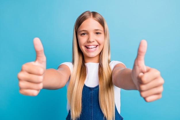 Nahaufnahme foto von ziemlich optimistischen teenager blonden langen haaren mädchen daumen hoch tragen weißes t-shirt isoliert über pastellblauem hintergrund