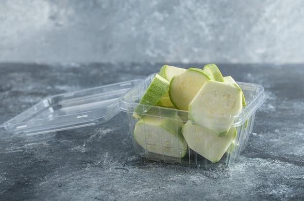 Nahaufnahme foto von zucchinischeiben in plastikbehälter.