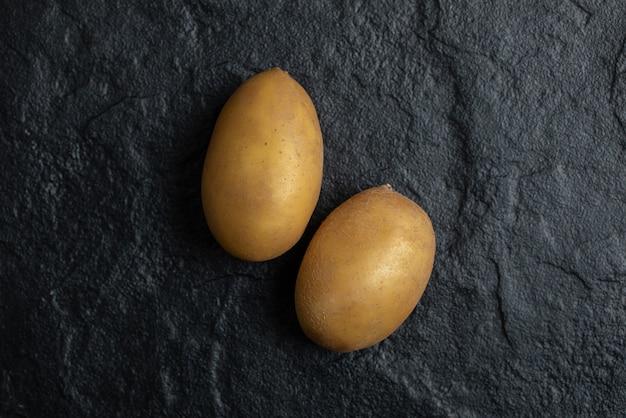 Nahaufnahme foto von zwei frischen kartoffeln auf schwarzem hintergrund.