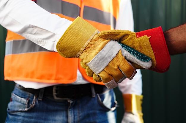 Nahaufnahme foto von zwei männern baumeister in arbeitskleidung händeschütteln