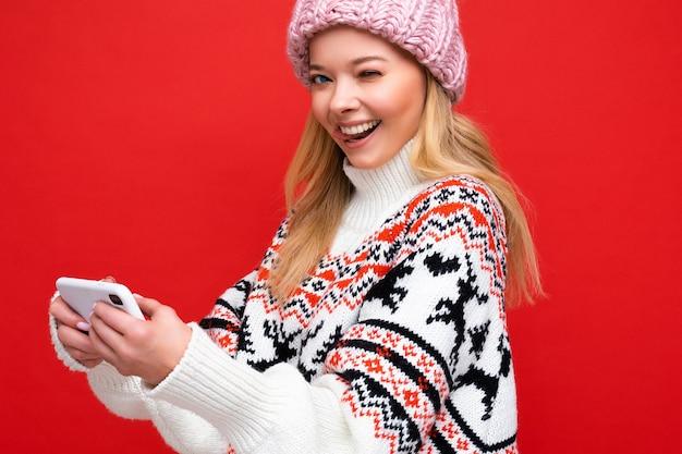 Nahaufnahme foto von zwinkernden schönen lächelnden jungen blonden frau mit warmer strickmütze und warmem winterpullover, die isoliert über rotem hintergrund steht und spiele über das smartphone mit blick in die kamera spielt.