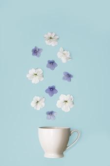 Nahaufnahme-fotokonzept. eine weiße tasse auf einem weichen blauen hintergrund wird mit fallenden blumen gefüllt. gesunde ernährung, körperreinigung, vegetarismus, selbstpflege, spa-schönheitssalon, kräutertees, schönheitsbehandlung
