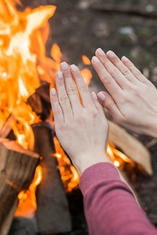 Nahaufnahme frau, die am lagerfeuer wärmt